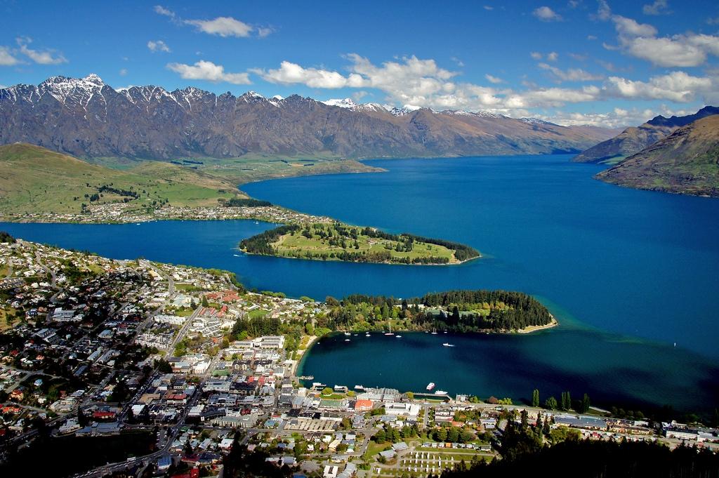 """<% pageTitle %>"""" /><br /> photo: Bernard Spragg. NZ </p></blockquote> <p>ワカティブ湖湖畔に沿うように位置しており、街全体はリマーカブルス山脈を代表とする山々に囲まれています。1年通して観光客や世界各国の移住者で賑わうクイーンズタウンですが、季節により楽しみ方も様々です^^<br /> 夏(12~2月)は、数多くのアクティビティが体験できるチャンスです。トレッキング(ハイキング)を始め、ジェットボートやスカイダイビング、バンジージャンプなど、大自然と一体化するチャンスが目白押し。日照時間もとても長く、夜は9時過ぎまで明るいので得した気分になります。<br /> 冬(6~8月)は、スキーやスノーボードのリゾート地して国内外らのスキーヤー、スノーボーダーが集まります。<br /> またニュージーランドの誇る世界遺産「ミルフォード サウンド」のツアー拠点の街としても有名です。<br /> クイーンズタウンには空港があり、街中心部へは車やバスで約25分です。<br /> (宿泊先によっては空港送迎のシャトルバスがあります。)</p> <h3 id="""